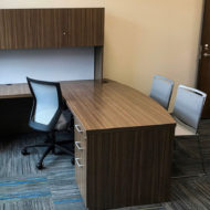 Run II mid-back chair behind a wood laminate L-shaped desk. There are two guest chairs placed in front of the desk, with the exit door off to the side.