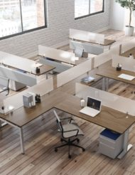 Overhead view of an open office plan, consisting of long benching for 6 or more workstations. Straight (model) screens are placed at the front and the sides of the L-shaped workstations. Windows bring in sunlight.