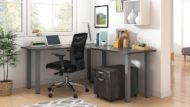 Studio shot of OTG's Home Office, with an L-shaped desk with a tungsten metal frame. The surface is finished in Artisan Grey. A matching set of drawers has been rolled under the desk, at the left of the mesh back chair. To the left of the laptop is a set of books and an OTG LED Desk lamp in the corner.