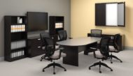 Studio photography of Offices to Go furniture in a conference area. A racetrack shaped table is in the center, with 6 high-back chairs placed around it. On the far wall, a presentation board has one of its double doors open, revealing a white board underneath. At the left is a matching mixed storage unit, with a tall book case at each side, and a flat screen TV directly above. The furniture uses an American Espresso finish.