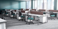 Open office space, featuring two rows of desks. A Run II mid-back office chair is placed at each work area, a teal green seat cushion and black mesh back.