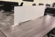 """Work table with the 15"""" tall Straight(model) space divider. It has rounded corners and its frosted glass conceals the area in front."""