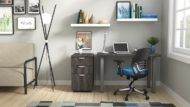 """Studio shot of OTG's Home Office Setup, which has a 24"""" x 48"""" work table placed in the corner by the window. At the left is a set of pedestal drawers. The third (top) drawer has a lock on it. Both the desk and pedestal drawers are finished in an _____. A simple mesh-back office chair is pulled up to the laptop, with a LED lamp next to it."""